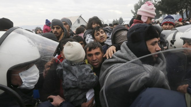 Des policiers tentent de contenir des réfugiés.
