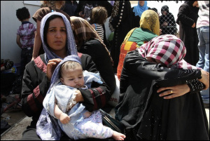 Families fleeing the violence in the Iraqi city of Mosul wait at a checkpoint in outskirts of Arbil