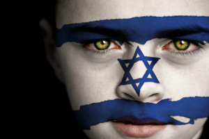 Portrait of a boy with the flag of Israel painted on his face.